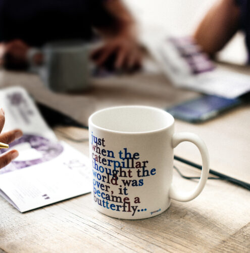 Picture of a mug on a table. The writing on the mug says: