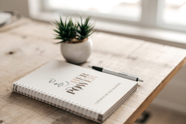 Build a Dream #HerPower Journal - Journey of Self Mastery - on a table with a plant and pen.