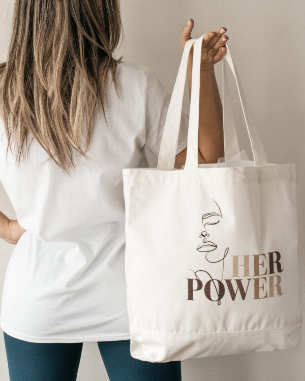 Build a Dream #HerPower Canvas Tote being held by a person