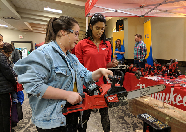 Raquel McLaren, Field Marketing rep with Milwaukee Tool, helps a student try a chainsaw at Build a Dream in Kitchener, Ontario.