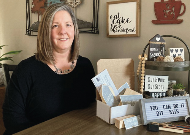 Lisa Miller of You Can Do It DIY Kits seated at a table with some of her wooden sign kits.