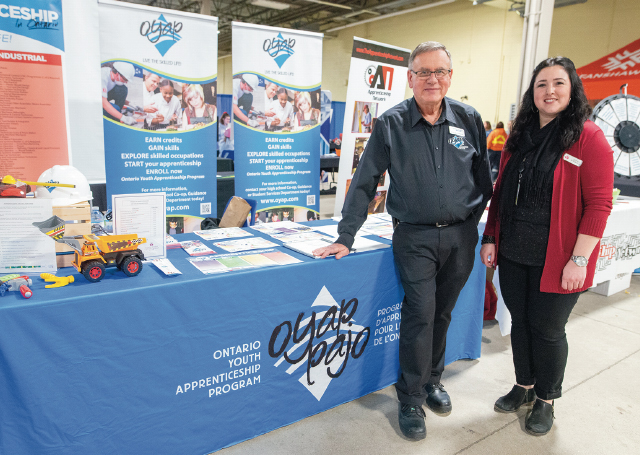 OYAP Coordinator Mark Brotherston & coworker stand at their booth at Build a Dream London inside the Agriplex.