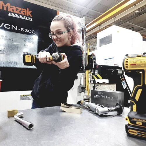 Rebecca Chenier holding a drill outside of her machine at Centreline