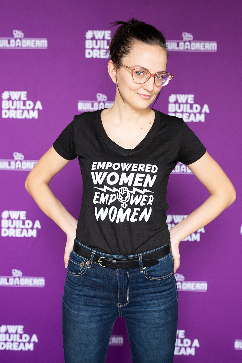 "Machinist Rebecca Chenier wearing a black shirt that reads, ""Empowered Women Empower Women"""