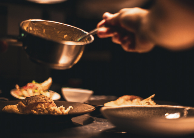A chef dishing up food into plates.