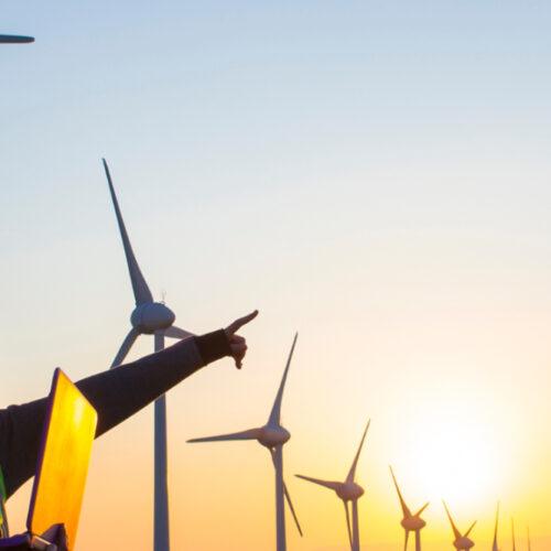 A male and female worker in a wind turbine field.