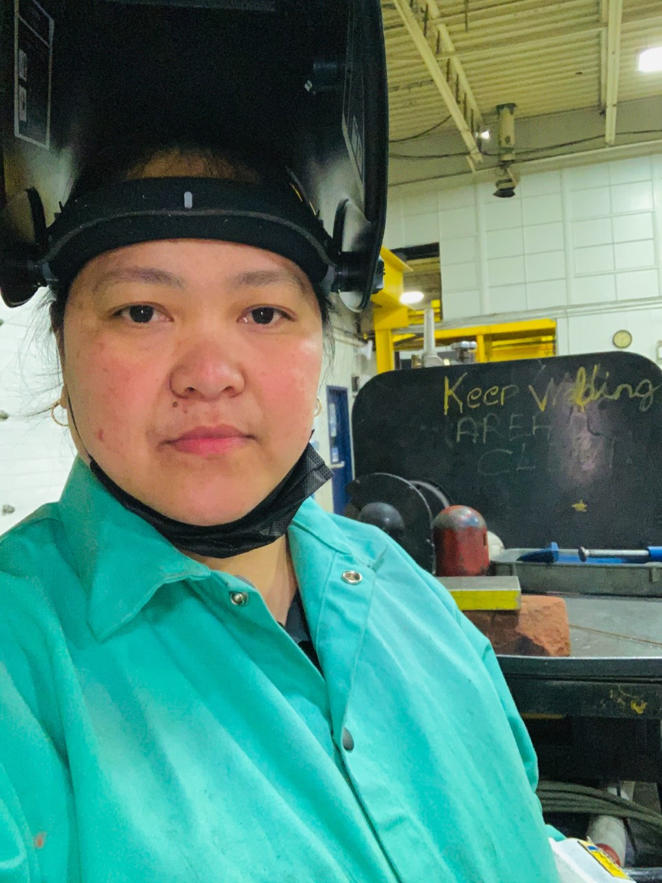 Marnie Bacharo at work wearing a welding helmet flipped up and a coat.