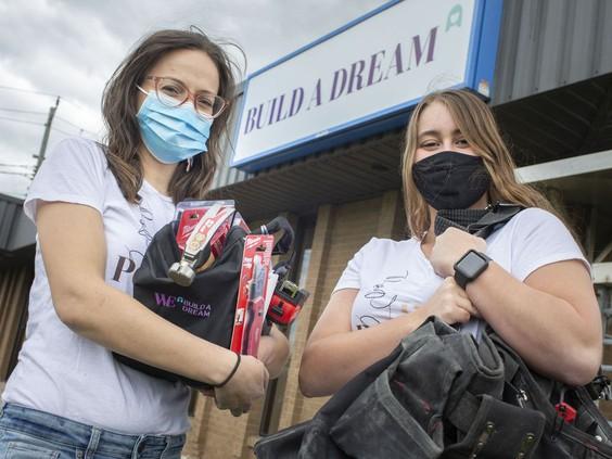 Windsor Star photo of tradeswomen Rebecca Chenier & Delaney Krieger holding #HerPower Tools prize bags.