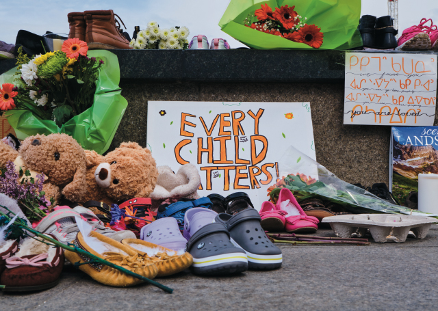 Photo from Parliament Hill showing flowers and shoes and a sign that says,