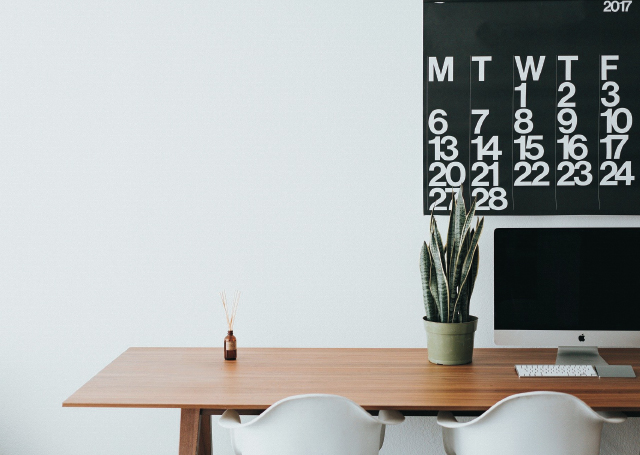 A desk with a plant and monitor with 2 chairs and a calendar on the wall.