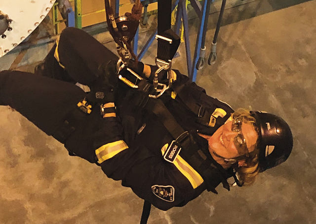 Firefighter Debra Rogers of the Campbell River Fire Dept in Britiish Columbia rappelling in full uniform.